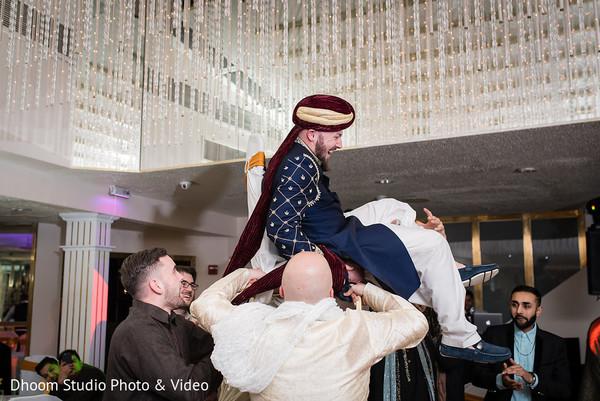 Indian groom being lifted by his groomsmen.