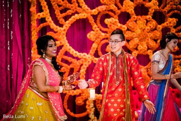 Indian bride and groom joyfully dancing