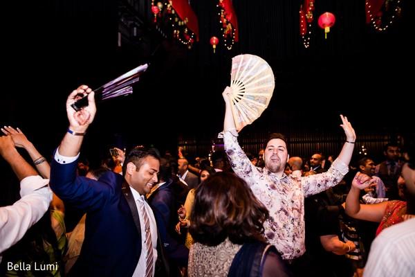 Joyful Indian wedding guests dancing capture