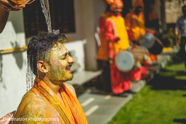 Indian groom having water pour on to his head capture.