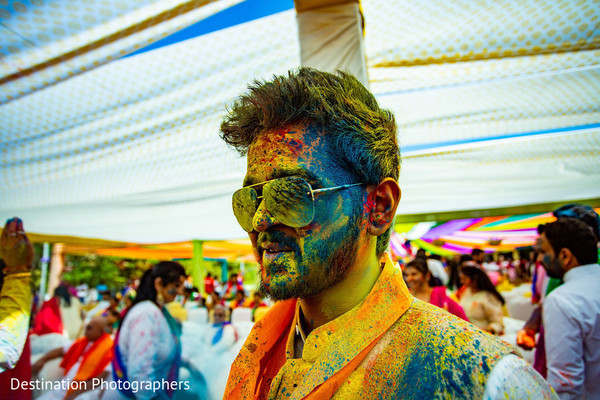 Impresive indian groom smeared with paint at haldi.