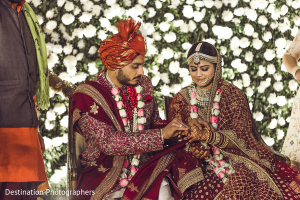 Enchanting Indian groom putting ring to bride.