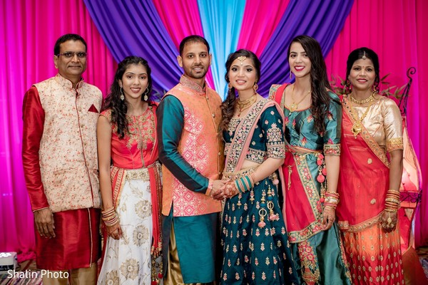 Enchanting Indian couple posing with relatives.