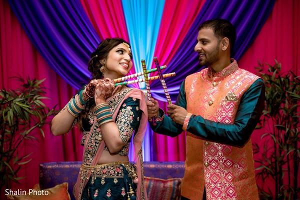 Marvelous capture of Indian couple holding dandiya sticks.