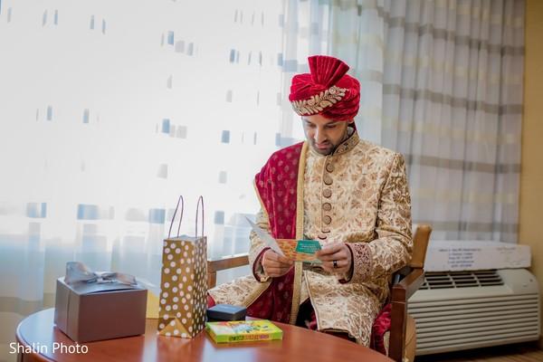 Joyful Indian groom reading bridal card.
