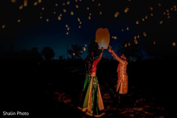 Sweet Indian couple lifting a sky lantern.
