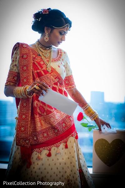 Sweet indian bride reading groom's card