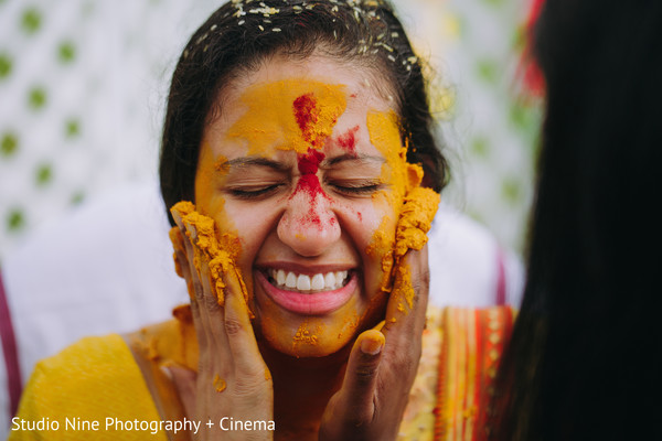 Indian bride is smeared in yellow turmeric paste at haldi ritual