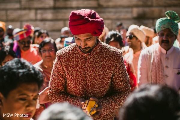 Enchanting Indian groom holding the wedding decorated nariyal.