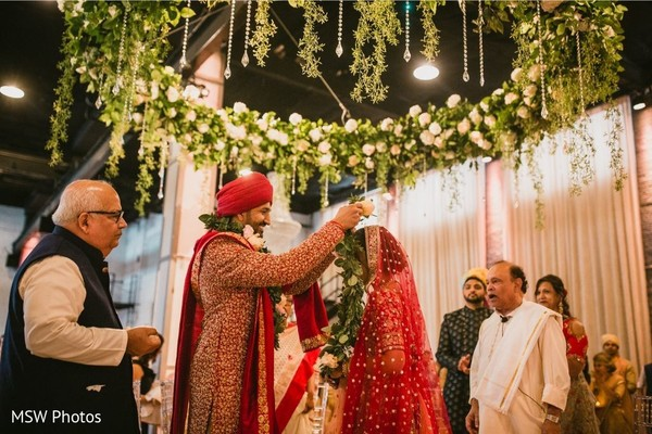 Enchanting Indian couple exchanging garlands.