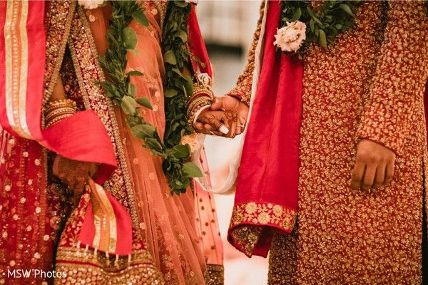 Closeup capture of Indian couple holding hands at ceremony.