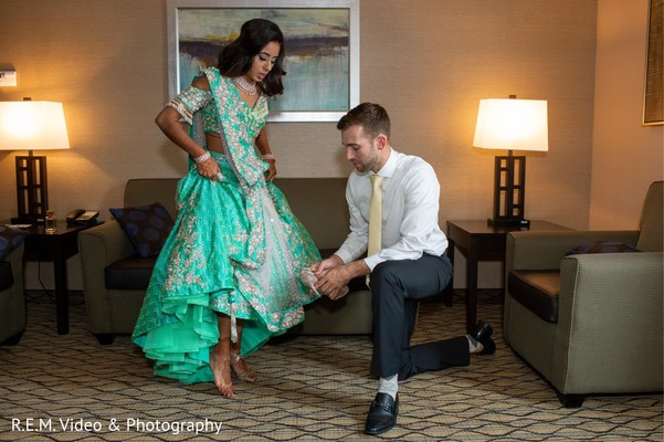 Indian groom putting shoes to bride.