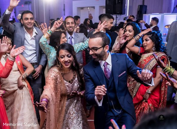 Joyful guests, bride and groom dancing photography