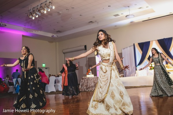 Indian bride dancing with bridesmaids on her wedding reception party