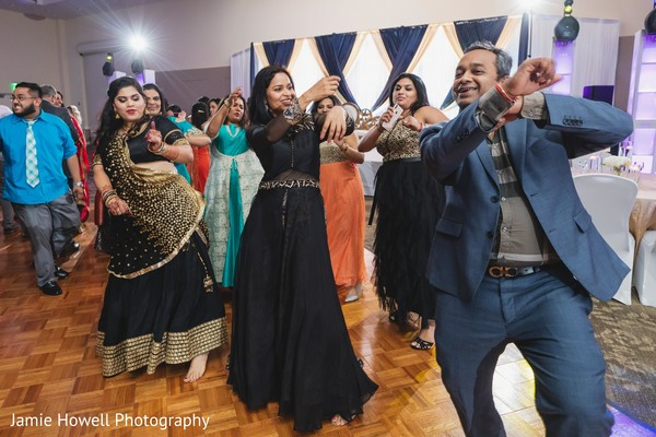 Cheerful indian bride dancing with guest