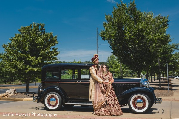 Indian couple posing in front of their beautiful transportation