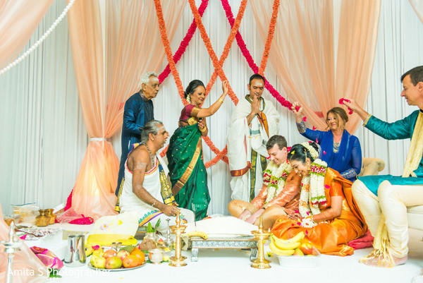 Indian couple receiving blessings during their wedding ceremony.
