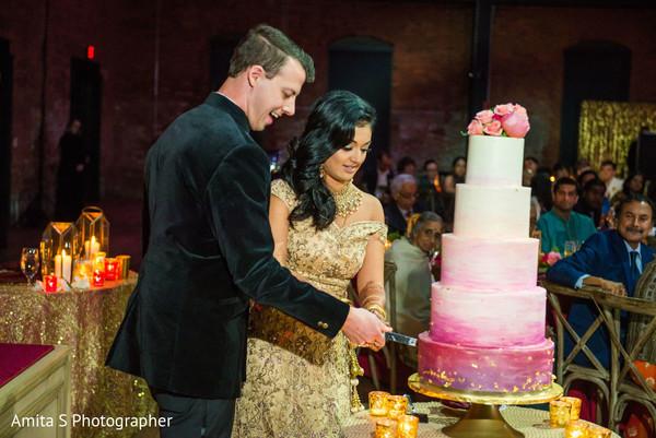 Indian couple cutting the wedding cake.