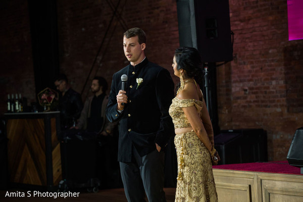 Indian groom giving speech during reception.
