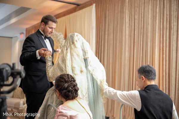 Elegant indian groom helping bride
