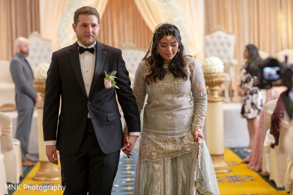 Indian bride and groom walking out from the ceremony isle