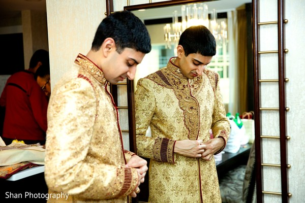 Charming Indian groom getting his sherwani on.