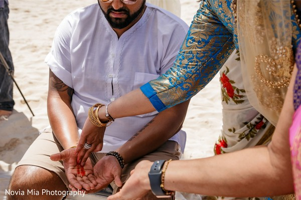 Indian groom getting red lines on his hands at Haldi.