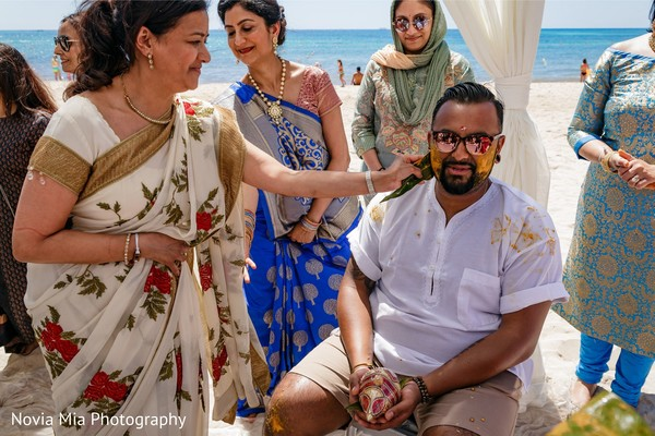 Indian groom getting turmeric paste on his face.
