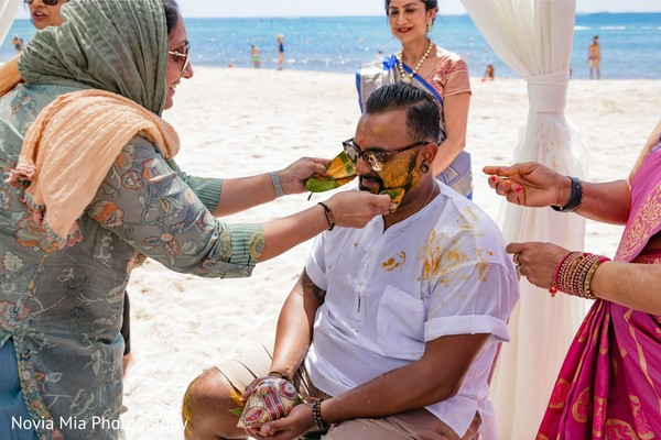 Indian relatives putting turmeric paste on Indian grooms face.