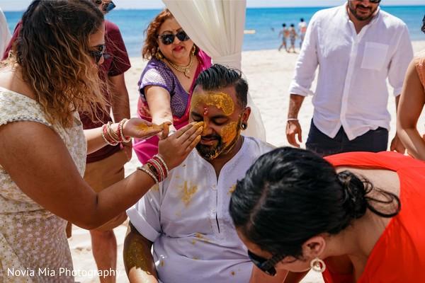 Haldi ritual where groom gets turmeric paste on face.