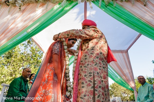 Charming Indian groom putting garland to bride.