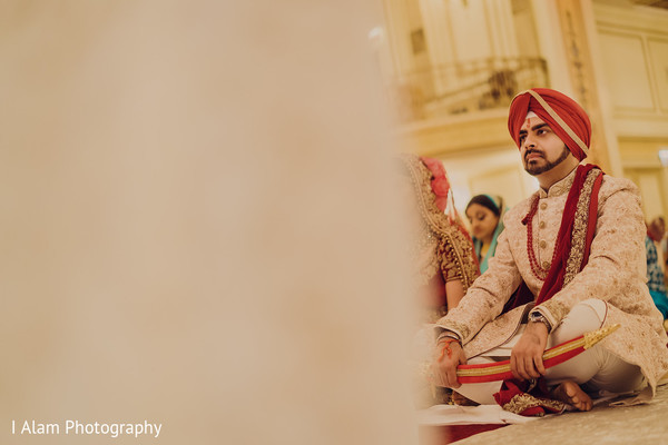 Groom holding the kirpan during the Indian wedding.