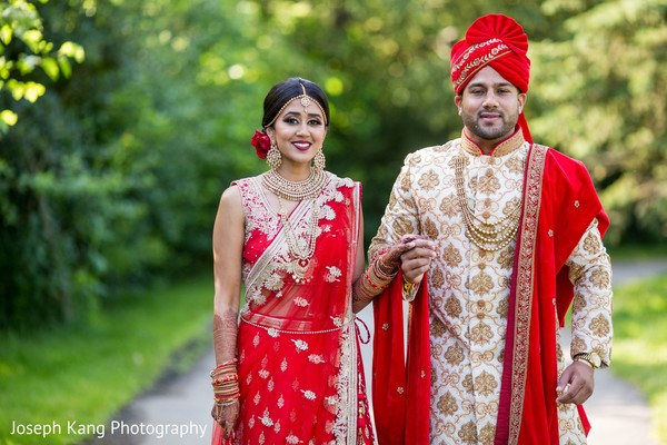 Indian bride and groom outdoors posing for pictures.