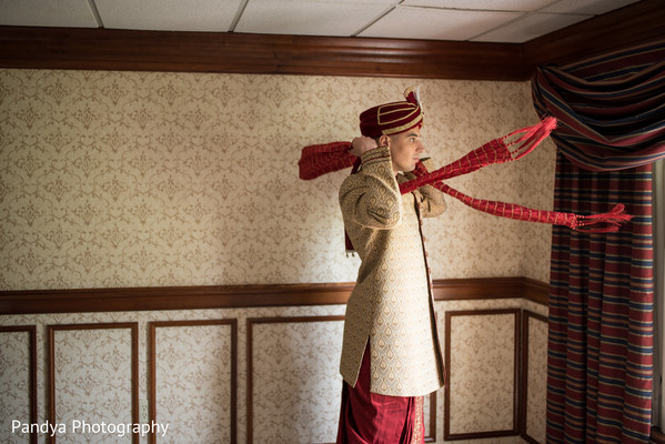 Indian groom putting scarf on.