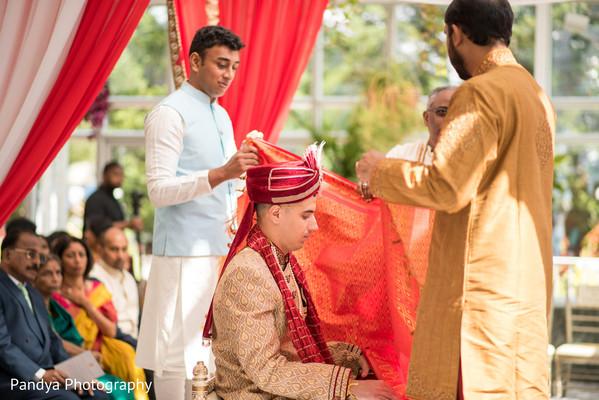 Indian groom meditating during wedding ceremony.