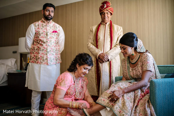 Groom's mother putting stunning anklet on Maharani.