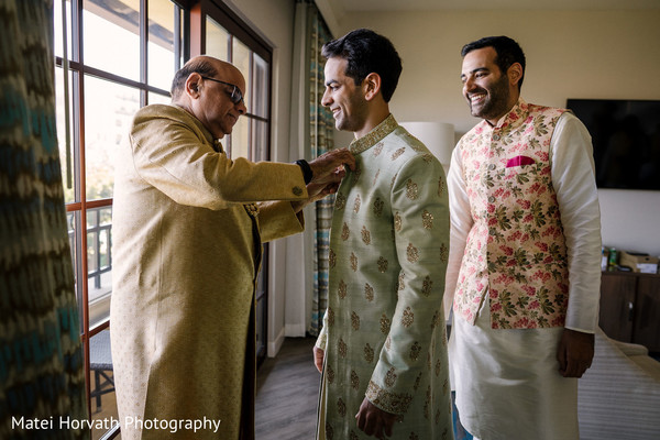 Indian groom being assisted by his relatives.