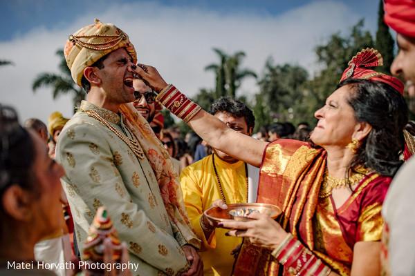 Maharani's mother pinching groom's nose.
