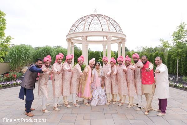 Groomsmen wearing peach sherwanis posing with the Indian newlyweds.