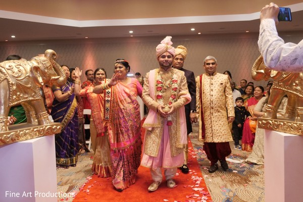 Raja wearing a beige and coral sherwani during his entrance.