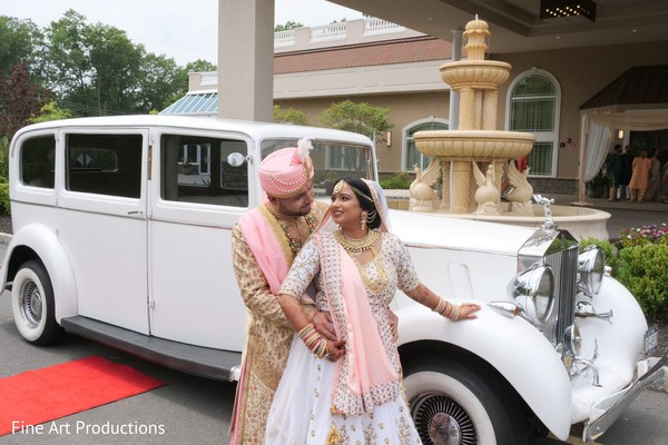 Maharani with Indian groom posing by their transportation.
