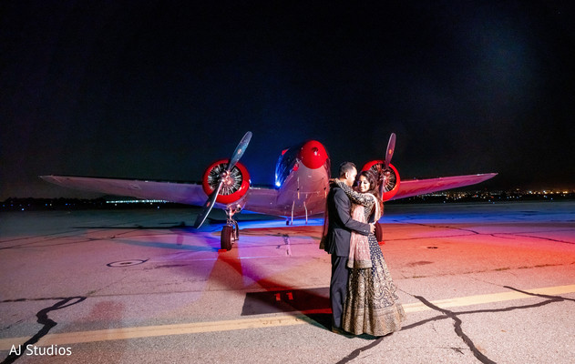 Indian couple posing in front of a light aircraft