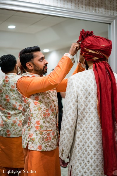Indian groom being assisted with the ceremonial pagri.