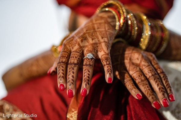 Indian bride showing her engagement ring and mehndi art.
