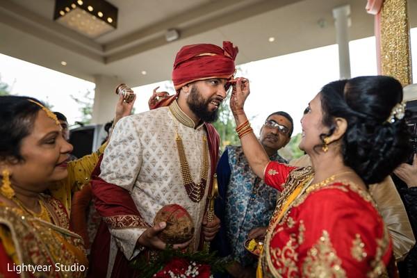 Indian groom receiving the bindi after Baraat.