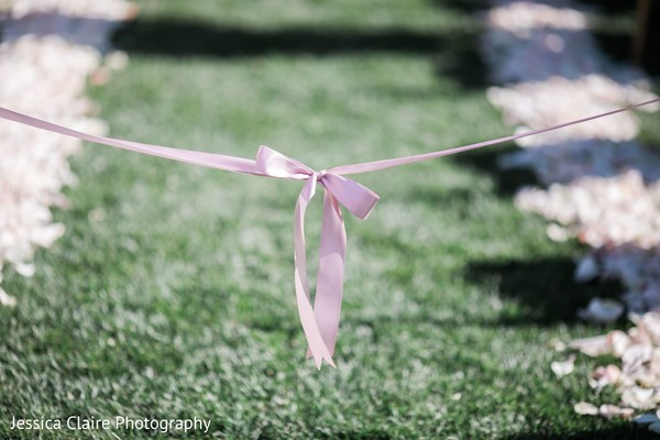 Closeup capture of Indian wedding aisle pink bow.