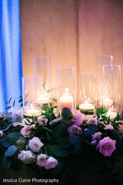 Pink roses and white candles at Indian wedding decoration.