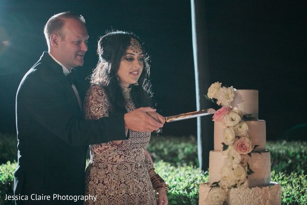 Indian wedding reception cutting the cake moment.