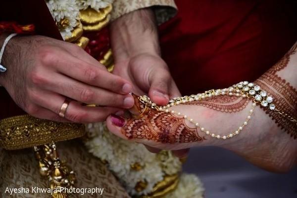 Indian groom putting ring to toe bride ritual.