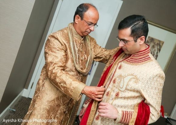 Indian groom putting on his ceremony outfit.